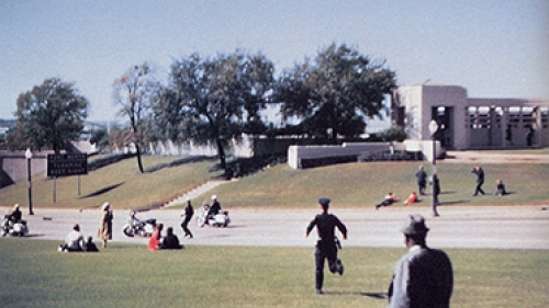 Film frame from home movie footage shot by Mark Bell on November 22, 1963, seconds after the Presidential motorcade had passed. The grassy knoll, from which many witnesses heard gunshots, is in the background. (Courtesy of Rauner Special Library)