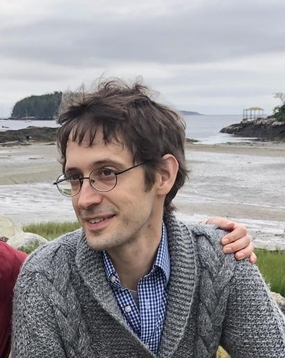 Sebastiaan looking sideways on a background of Maine at low tide