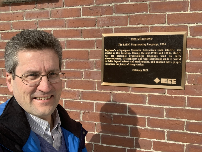 David Kotz '86, the Pat and John Rosenwald Professor of Computer Science, stands next to the IEEE Milestone plaque outside the south entrance to the Collis Center after it was installed earlier this month.